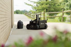 robot approaching backpack outdoors