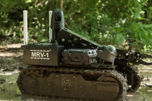 black robot covered with mud in woods, product photography