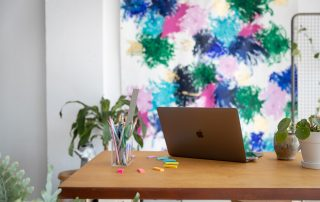 macbook on a modern wood work table in front of a modern art canvas, ways to build your business