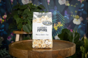 wv product photography, gourmet popcorn in front of a dark floral backdrop