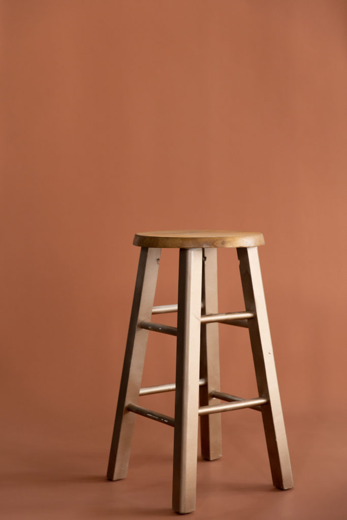 wooden stool in front of a henna seamless paper backdrop at wv photography studio