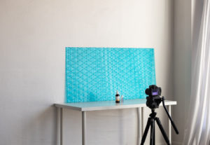 a camera set up to take product photos in front of bright blue textured backdrop