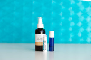 beauty products in front of bright blue texted backdrop