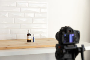 a camera set up to take product photos in front of a wood and tile backdrop