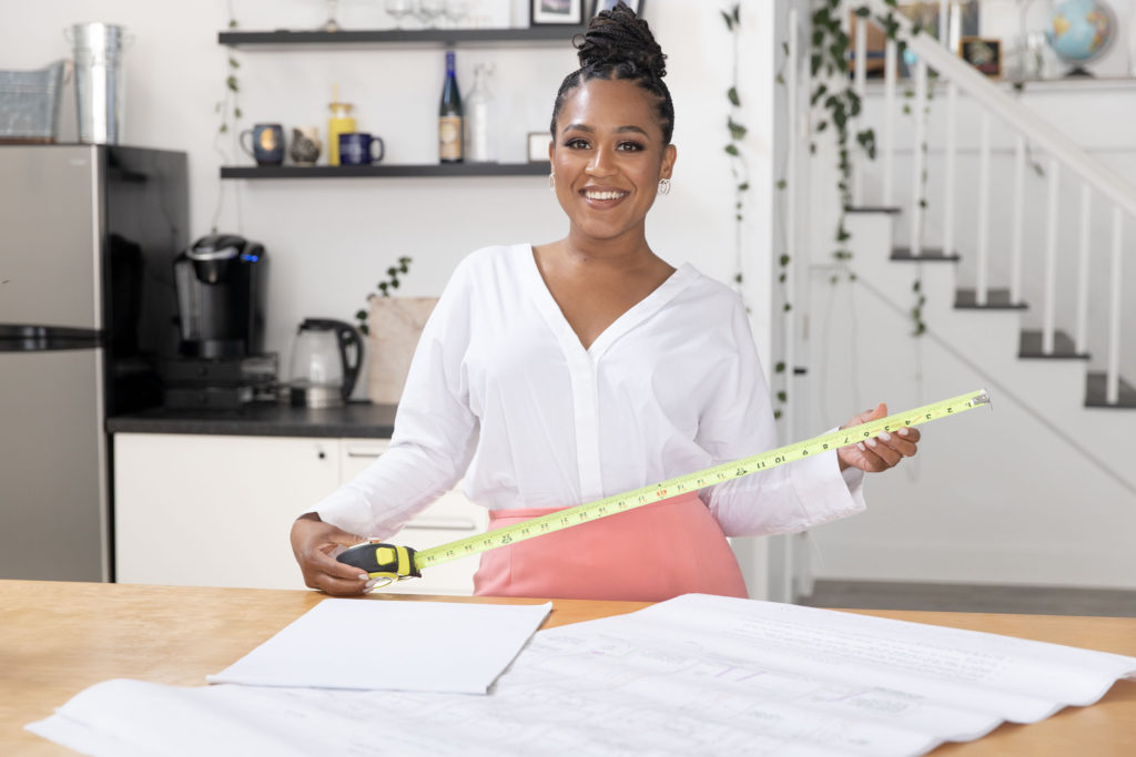 realtor with a measuring tape in a white kitchen