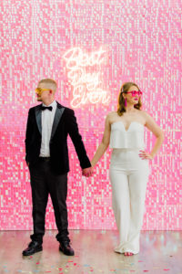 a bride in a white jumper and groom in a tux in front of a pink glitter wall and a neon best day ever sign