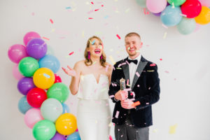a bride in a white dress and groom in a tax popping coloful confetti in a white space with colorful balloons