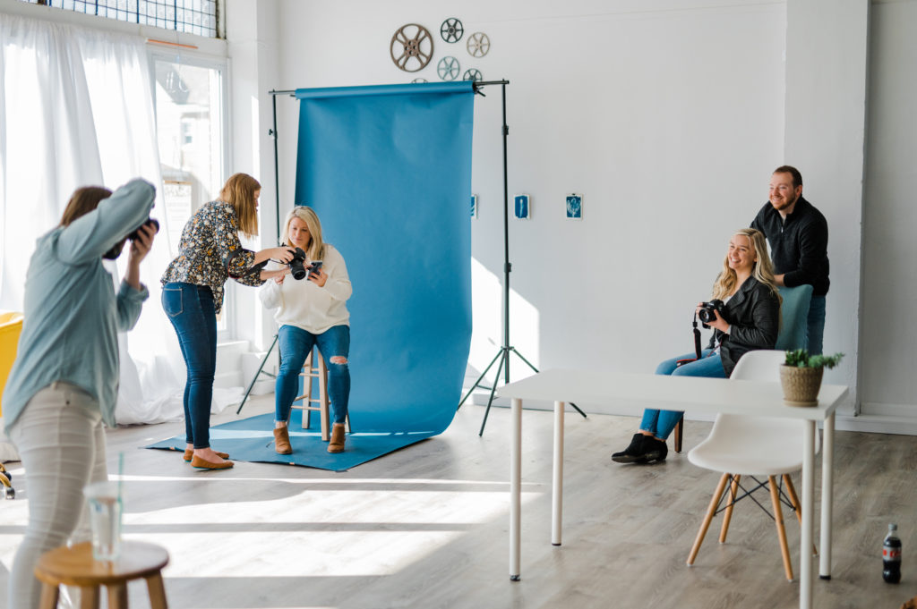 a group of photographers taking photos of each other in a bright white studio in front of a blue backdrop