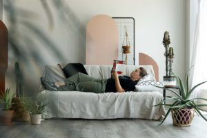 a woman reclined on a couch in a photography studio, reading a book