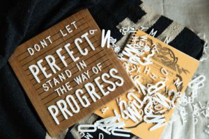 white letters on a brown letterboard spelling out progress over perfection.