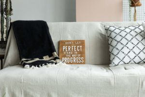 """a wooden letterboard with the phrase """"don't let perfect stand in the way of progress"""" on a sofa in a natural light photography studio"""