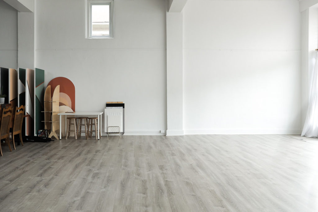 an open natural light space for photography in the 304 collective studio in fairmont wv with white walls a beutral gray floor and a collection of backdrops