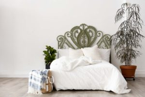 a photography set featuring sage green wicker headboard with a white bed and plants